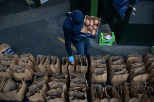 Man packing food bags for Feed The Frontline