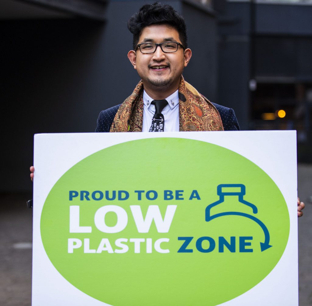 Yeohan kim holds a sign announcing the launch of London's first Low Plastic Zone (LPZ).