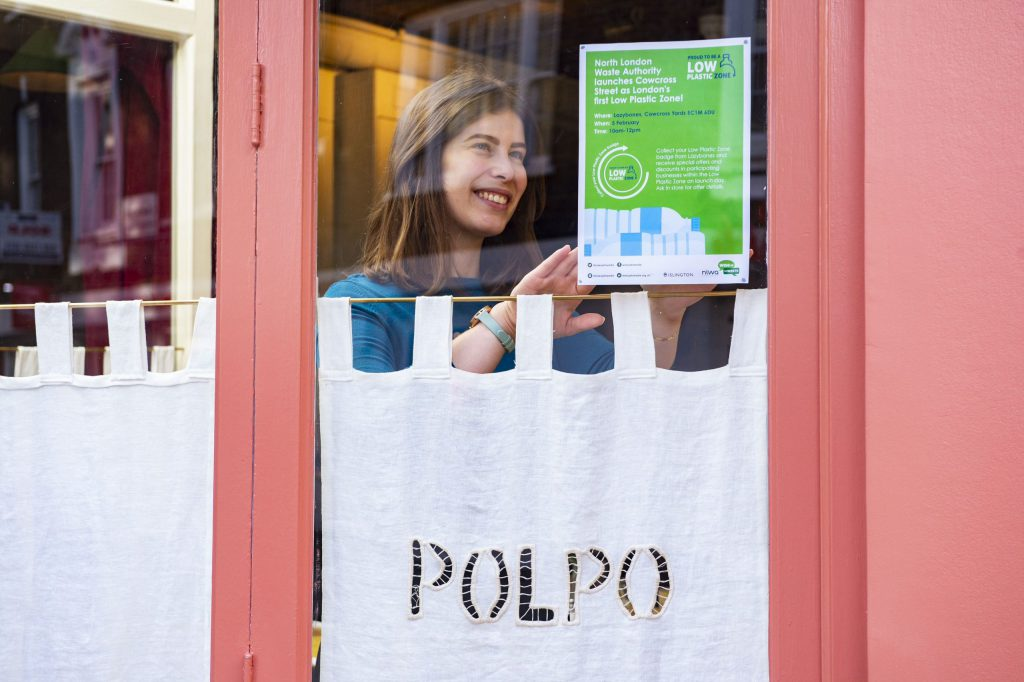 """Lady placing NLWA """"Low Plastic Zone"""" posters in her window"""