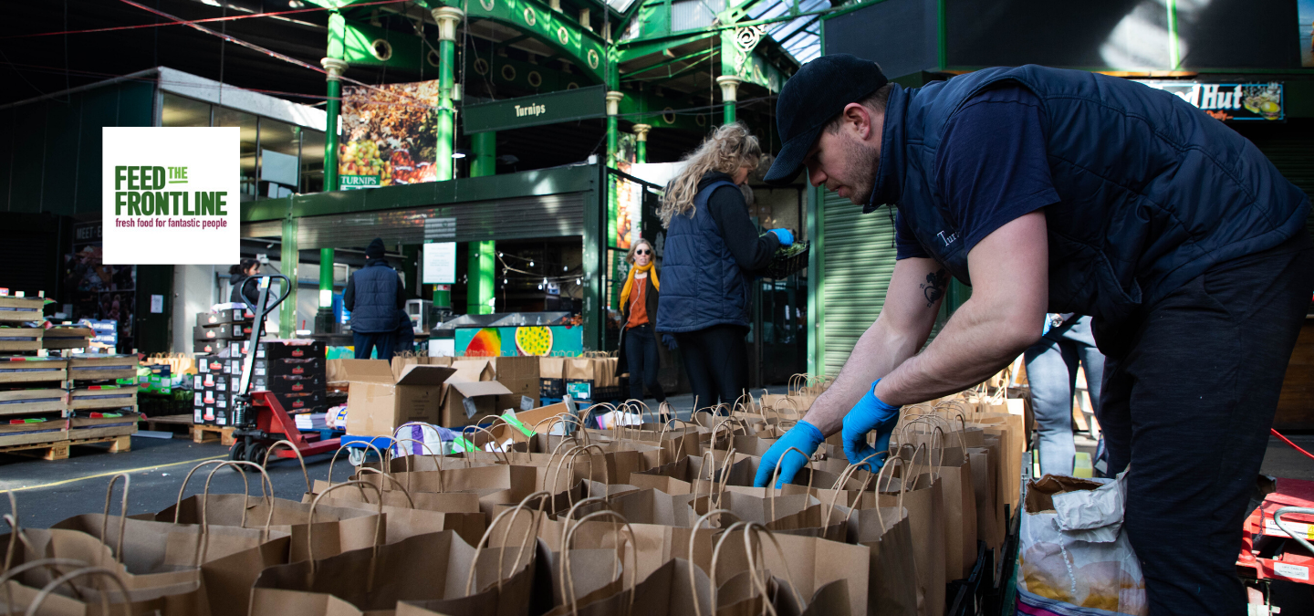 Man packing food bags to Feed the Frontline
